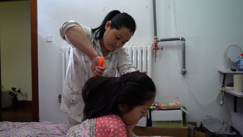 Ding Aihua combs her daughter's hair at their home in Heze, Shandong province, March 2019. Li Yang and Wang Haowei for Sixth Tone