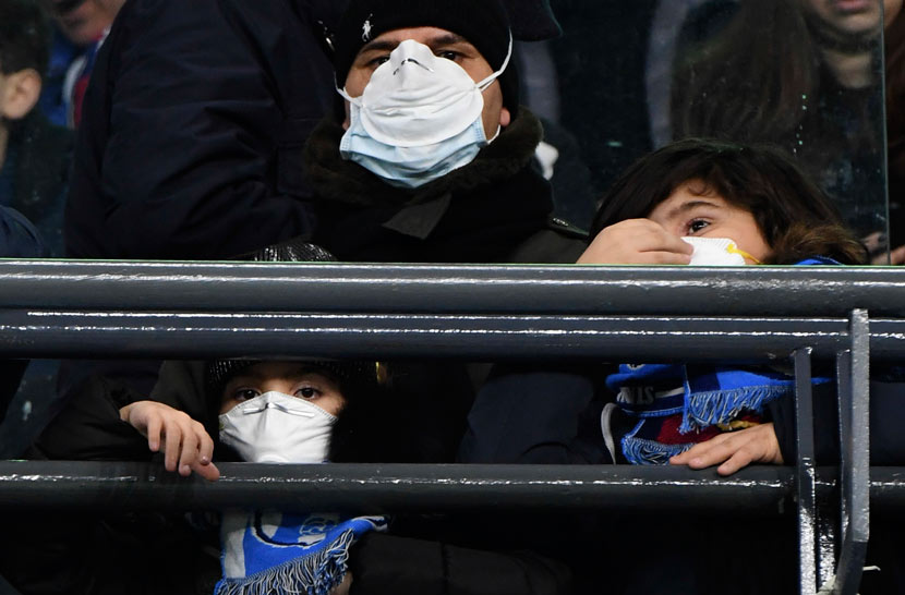 A family of soccer fans wearing face masks to guard against COVID-19 attend a Champions League match in Naples, Italy, Feb. 25,2020. Salvatore Laporta/IPA/IC