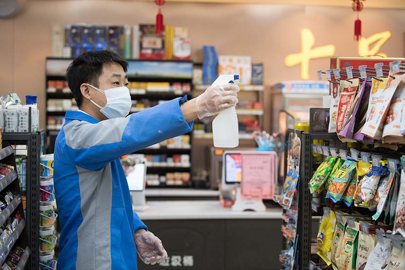 A staff member sterilizes a  convenience store in Wenzhou, Zhejiang province, Feb. 2, 2020. Xinhua