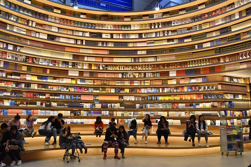 People browse for books at a new store with wraparound shelving units in Hohhot, Inner Mongolia Autonomous Region, April 21, 2019. IC