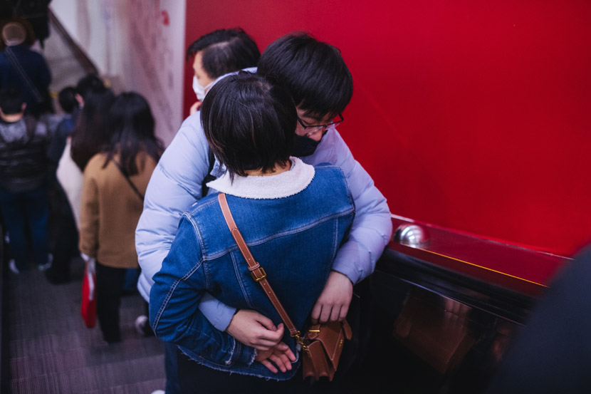A couple embraces on an escalator in Shanghai, Feb. 27, 2020. Wu Huiyuan/Sixth Tone