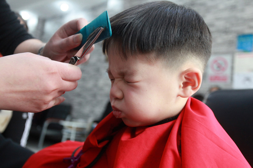 A child gets his bangs trimmed for the Longtaitou Festival in Yangzhou, Jiangsu province, Feb. 24, 2020. Held on the second day of the second month of the lunar calendar, Chinese traditionally mark the festival by getting a haircut. Meng Delong/IC