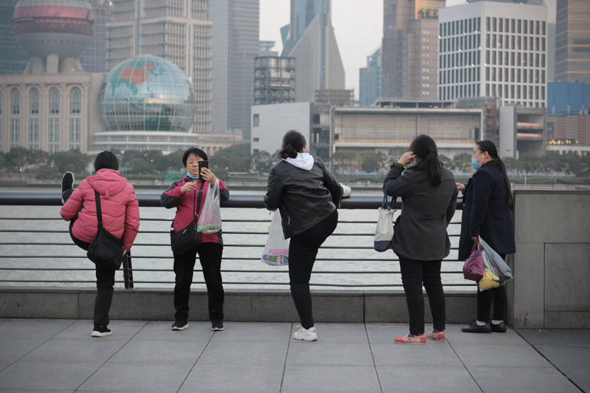 Sightseers enjoy the view from the Bund in Shanghai, Feb. 24, 2020. Chen Jianhui for Sixth Tone