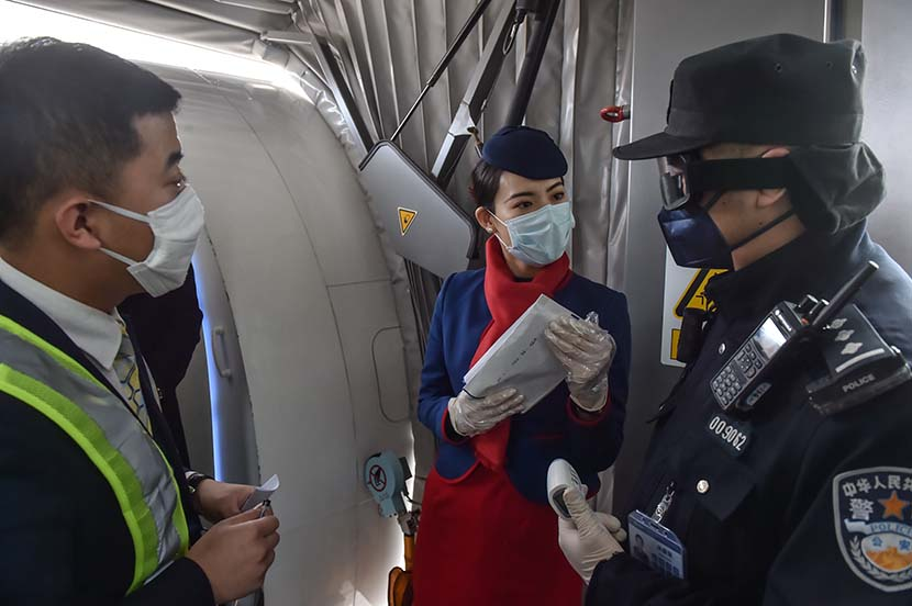 Police officers ask a cabin crew member for foreign passengers' personal information at Beijing Daxing International Airport, Feb. 1, 2020. Xinhua