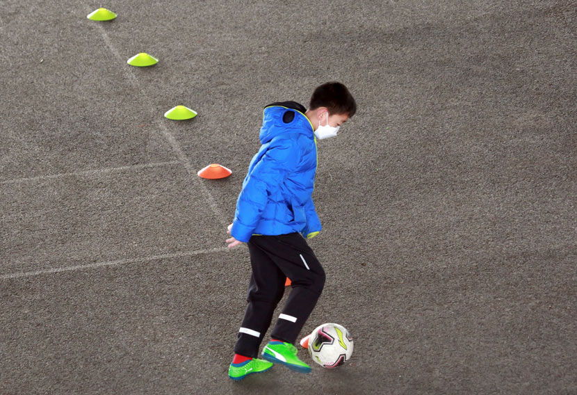 A boy practices his soccer skills in Shenyang, Liaoning province, Feb. 12, 2020. Huang Jinkun/IC
