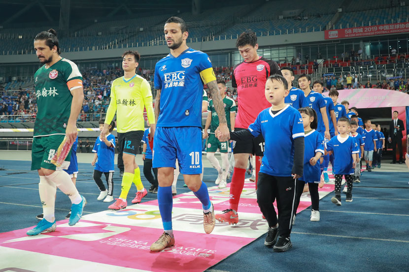 Players from clubs in Guangdong and Hebei provinces walk onto the field before a China League One match in Shijiazhuang, Hebei province, Sept. 22, 2019. IC