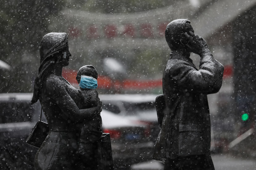 A mask has been placed over a child statue's face on a snowy day in Wuhan, Hubei province, Feb. 15, 2020. Yuan Zheng for Sixth Tone