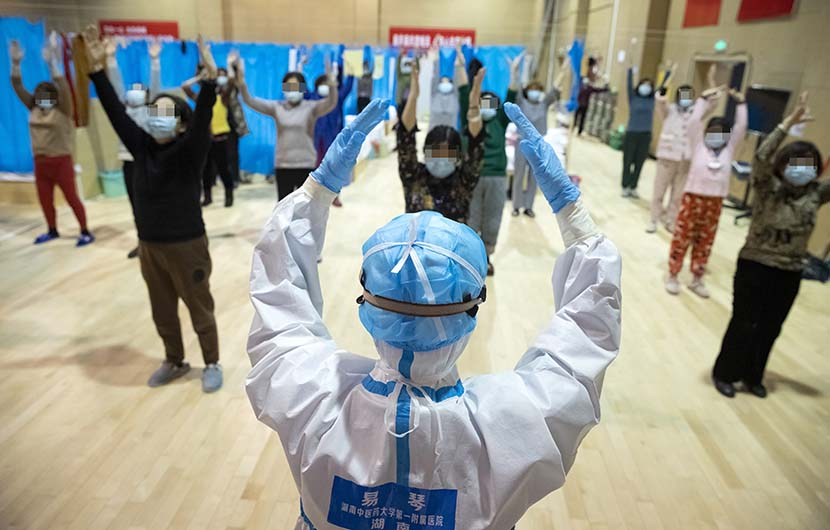 "A medical worker leads an exercise session for COVID-19 patients with mild symptoms at a temporary ""shelter hospital"" in Wuhan, Hubei province, Feb. 25, 2020. Shen Bohan/Xinhua"