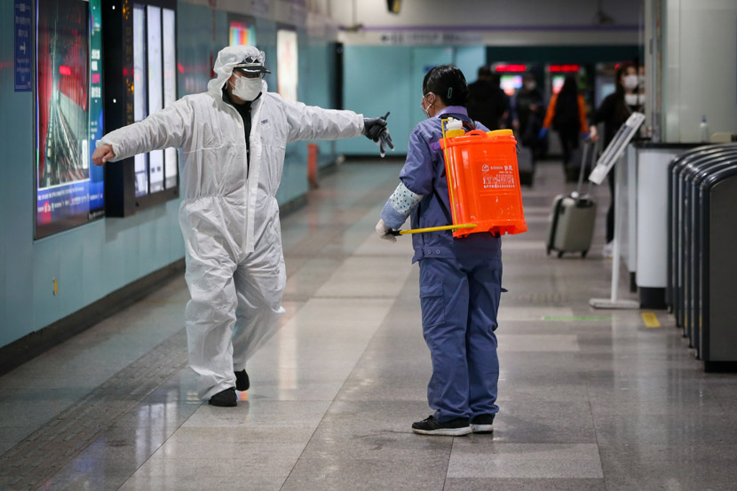A cleaner disinfects a subway worker in Shanghai, Feb. 14, 2020. Zhu Weihui for Sixth Tone