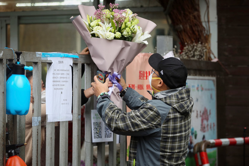 On Valentine's Day, a florist delivers a bouquet of flowers over the locked gate of a residential community in Shanghai, Feb. 14, 2020. Zhu Weihui for Sixth Tone