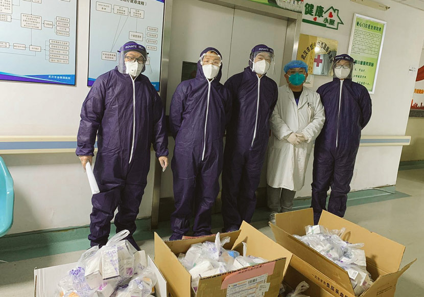 Volunteers and a medical worker pose for a photo at Jinyintan Hospital in Wuhan, Hubei province, 2020. Courtesy of MJ