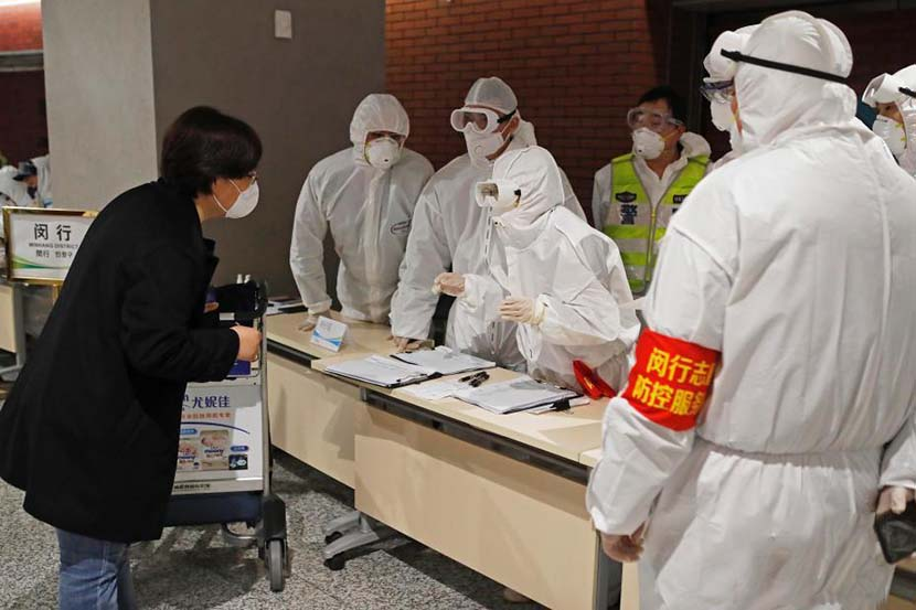 A woman registers at a public health checkpoint after passing through immigration at Shanghai Hongqiao International Airport, March 7, 2020. Yin Liqin/CNS