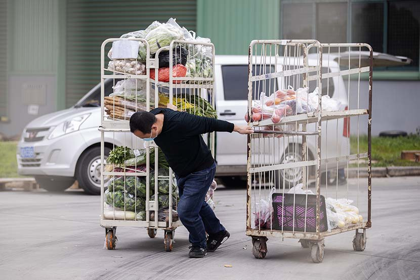 A man hauls two carts of vegetables in Wuhan, Hubei province, March 7, 2020. Xinhua