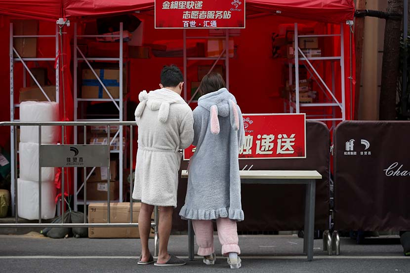 A couple in pajamas at their residential community's delivery pickup station in Shanghai, March 4, 2020. Zhu Weihui for Sixth Tone