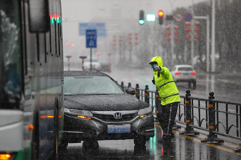 A police officer directs traffic in Wuhan, Hubei province, Feb. 15, 2020. Yuan Zheng for Sixth Tone