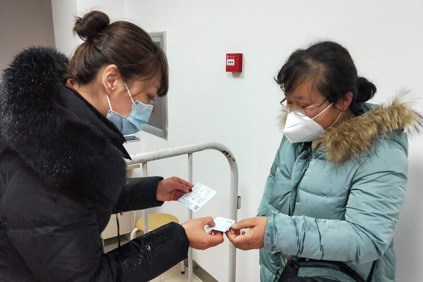 Liu Xuqing (left) checks a resident's tickets after she arrived in the community, in Shenyang, Liaoning province, February 2020. Courtesy of Liu Xuqing