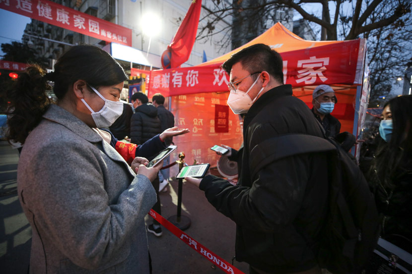 A social worker checks a QR code for monitoring health at the entrance of a residential community in Xi'an, Shaanxi province, March 9, 2020. Tian Ye/IC