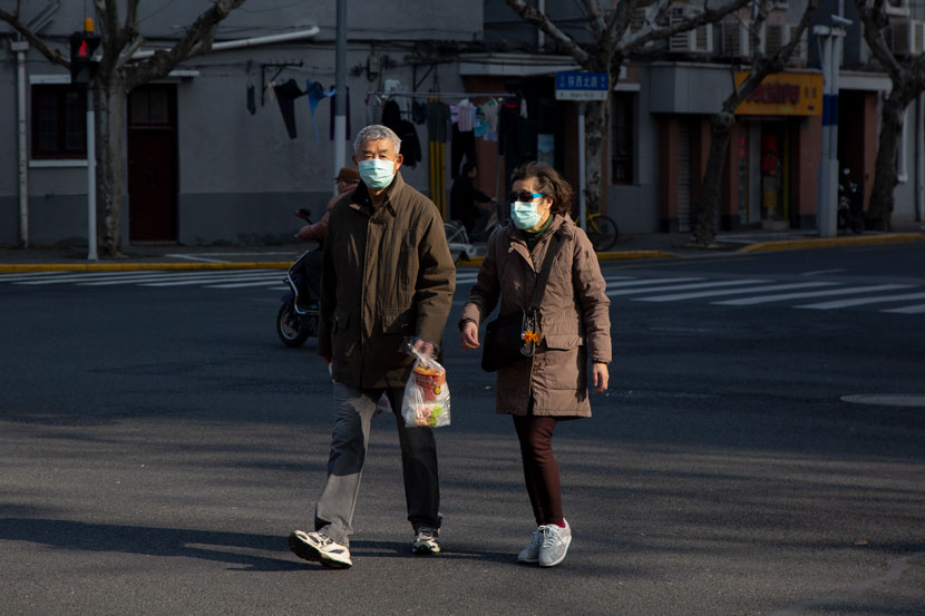 An elderly couple walks along a street in Shanghai, Feb. 12, 2020. Shi Yangkun/Sixth Tone