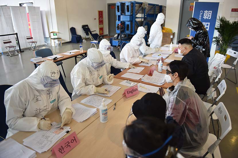Medical workers register incoming travelers for their compulsory two-week quarantine periods at the China International Exhibition Center in Beijing, March 14, 2020. Xinhua