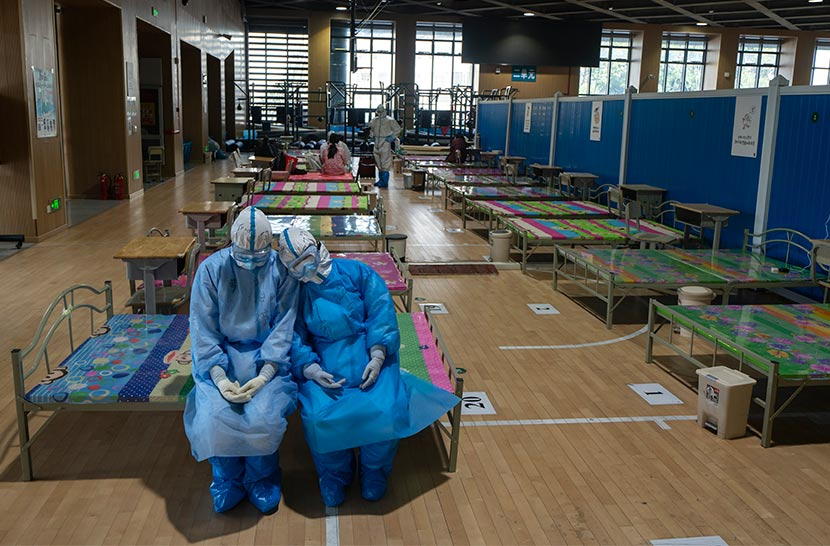 "Two medical workers dispatched from Qinghai province to aid with COVID-19 treatment and containment efforts rest at a closed-down ""shelter hospital"" in Wuhan, Hubei province, March 12, 2020. Xiao Yijiu/Xinhua"