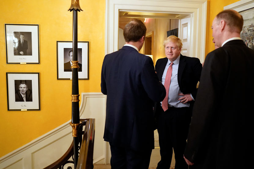 U.K. Prime Minister Boris Johnson (middle) speaks with officials after a press conference about the British government's response to the COVID-19 pandemic, London, March 17, 2020. Xinhua