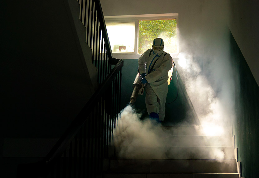 A medical worker sprays disinfectant in a stairwell of a building in Wuhan, Hubei province, March 10, 2020. Xiong Qi/Xinhua