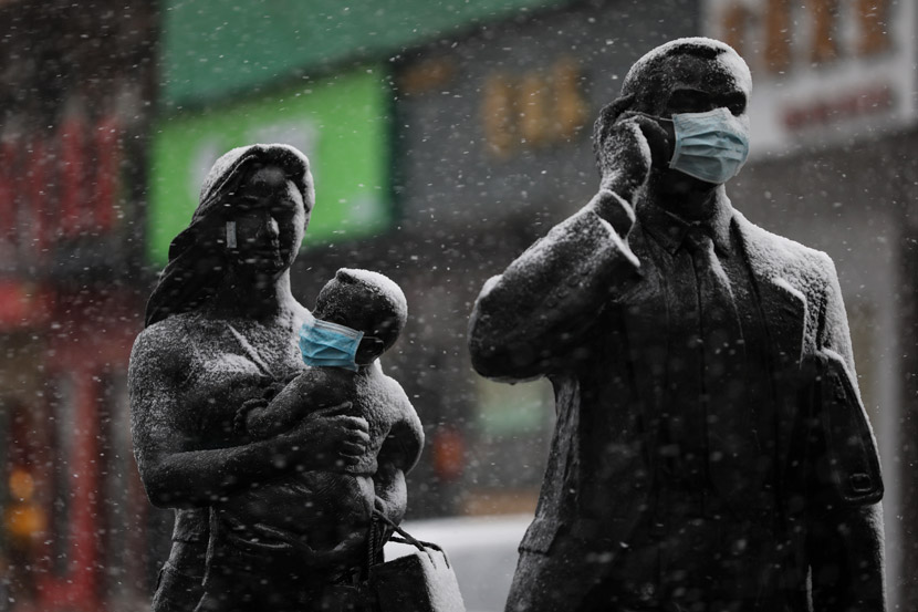 A mask placed over a child statue's face on a snowy day in Wuhan, Hubei province, Feb. 15, 2020. Yuan Zheng/Changjiang Daily
