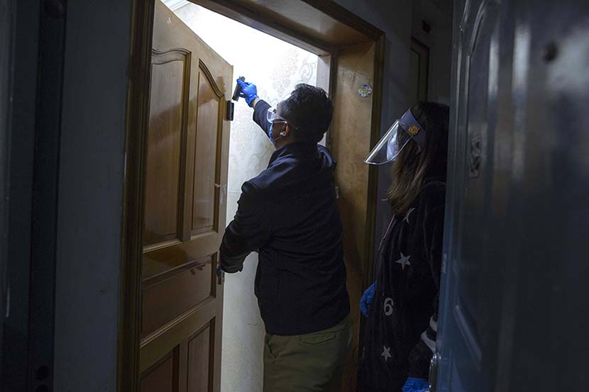 A neighborhood committee member installs electromagnetic sheets in the apartment of an Italian woman in Shanghai, March 18, 2020. The sheets are designed to monitor if an individual leaves their home. Ying Yi for Sixth Tone