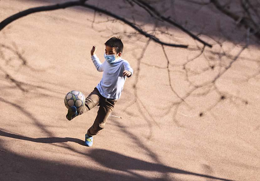 A boy plays soccer in a Beijing neighborhood, March 17, 2020. Xinhua