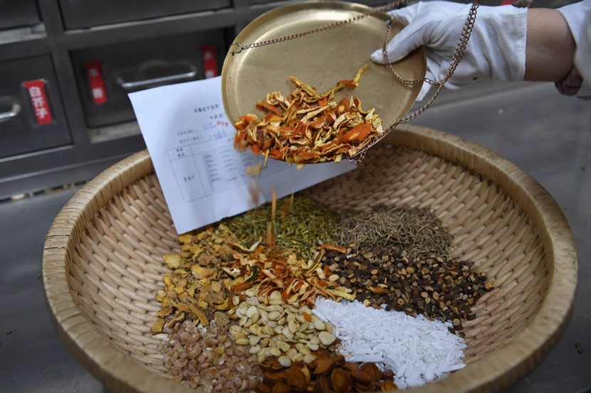 "A pharmacist checks the materials for the ""lung-cleansing decoction"" at the pharmacy in Anhui Province Hospital of Traditional Chinese Medicine in Hefei, Anhui province, Feb. 21, 2020. Zhang Dagang via Xinhua"