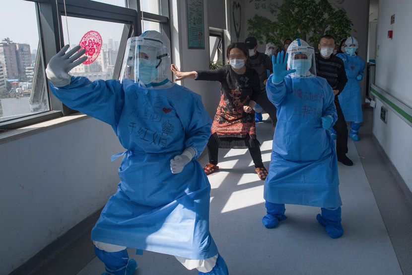 "Medical workers lead patients in a session of ""Baduanjin,"" one of the most common forms of meditative exercise qi gong, in the corridor of a hospital in Wuhan, Hubei province, March 19, 2020. Xiao Yijiu/Xinhua"