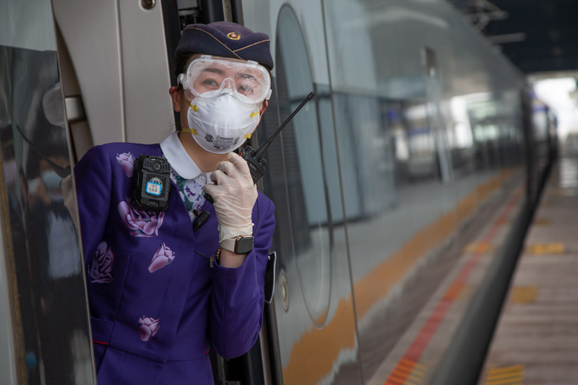 An attendant on a high-speed train at a railway station in Xiangyang, Hubei province, March 25, 2020. Yang Dong via Xinhua