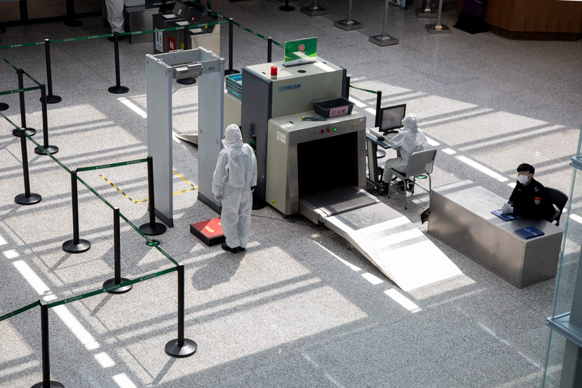 An airport security staff member waits for passengers at Shanghai Hongqiao International Airport, March 17, 2020. Shi Yangkun/Sixth Tone