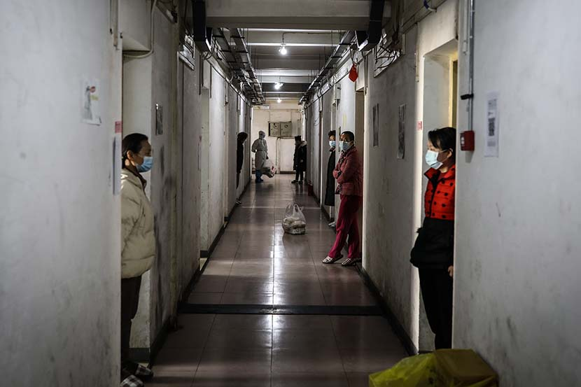Men rest along the gallery outside their rooms at the quarantine center set up in the dormitories of Wuhan Vocational College of Software and Engineering in Wuhan, Hubei province, March 13, 2020. Zhao Di/China Youth Daily
