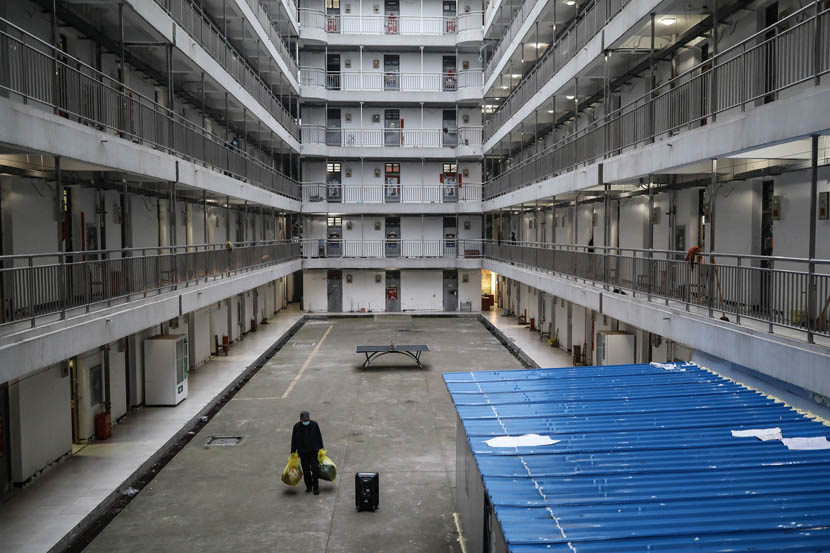 A man ready to be discharged carries his bags at the quarantine center set up in the dormitories of Wuhan Vocational College of Software and Engineering in Wuhan, Hubei province, March 13, 2020. Zhao Di/China Youth Daily