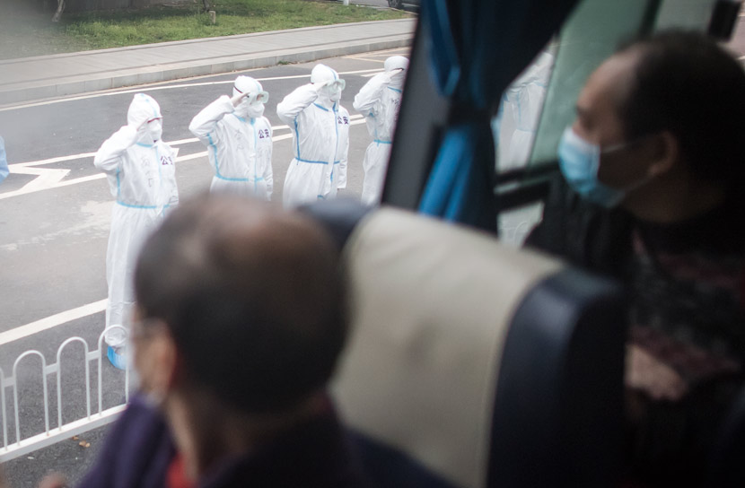 Policemen in protective gear salute recovered patients at the end of their quarantine periods in Wuhan, Hubei province, March 12, 2020. Xiao Yijiu/Xinhua