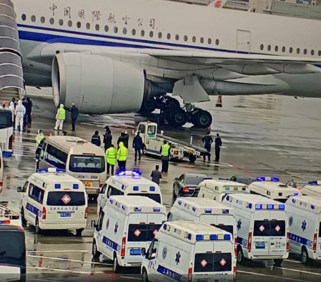 Ambulances are parked on the tarmac next to a commercial jet that arrived from Frankfurt, Germany, at Shanghai Pudong International Airport, March 11, 2020. Four feverish passengers and two others who had taken anti-flu medication before boarding were sent to designated medical facilities for screening and treatment. From @湾区零食工 on Weibo