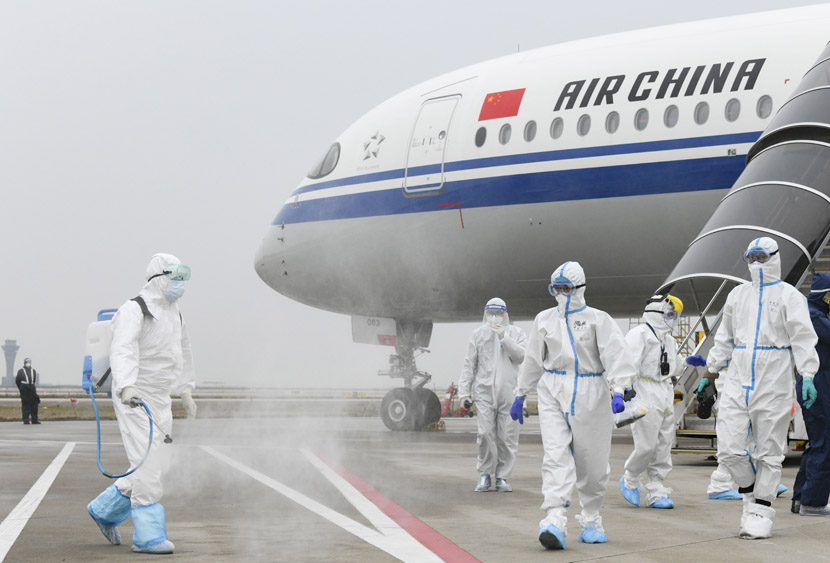 A worker in a hazmat suit sprays disinfectant outside a plane that arrived from Frankfurt, Germany, at Shanghai Pudong International Airport, March 13, 2020. Four feverish passengers and two others who had taken anti-flu medication before boarding were sent to designated medical facilities for screening and treatment. Zhang Chi/Jiefang Daily