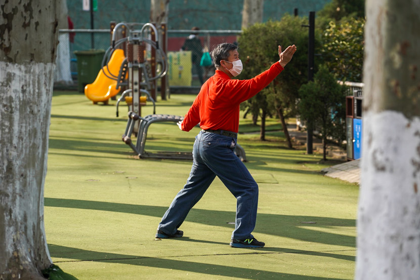 A masked man does his morning tai chi exercises on a playground in Nanjing, Jiangsu province, March 12, 2020. Residents are required to reserve time slots before using the public space. Li Bo/Xinhua