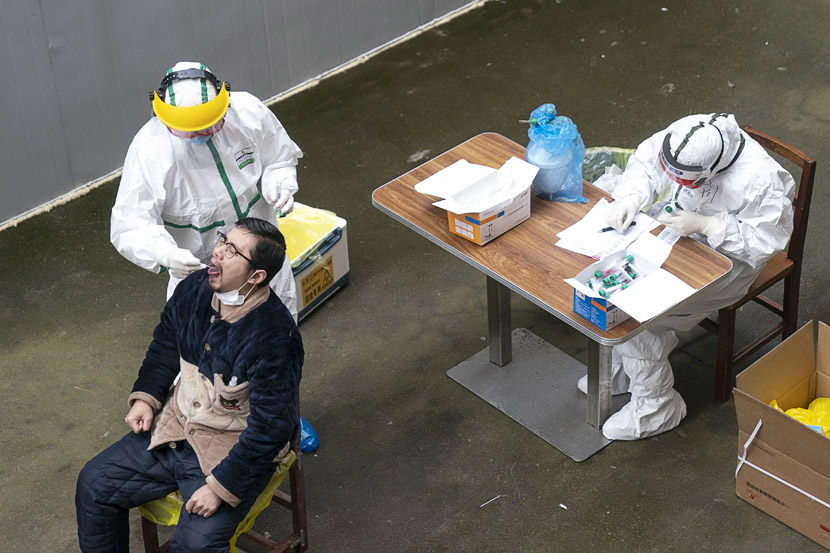 A medical worker takes a man's throat sample to conduct a COVID-19 nucleic acid test at a school in Wuhan, Hubei province, March 10, 2020. Xiong Qi/Xinhua