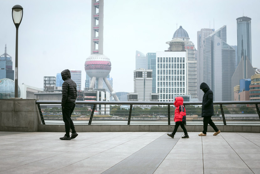 A family walks along the Bund in Shanghai, March 11, 2020. Lü Wei/IC