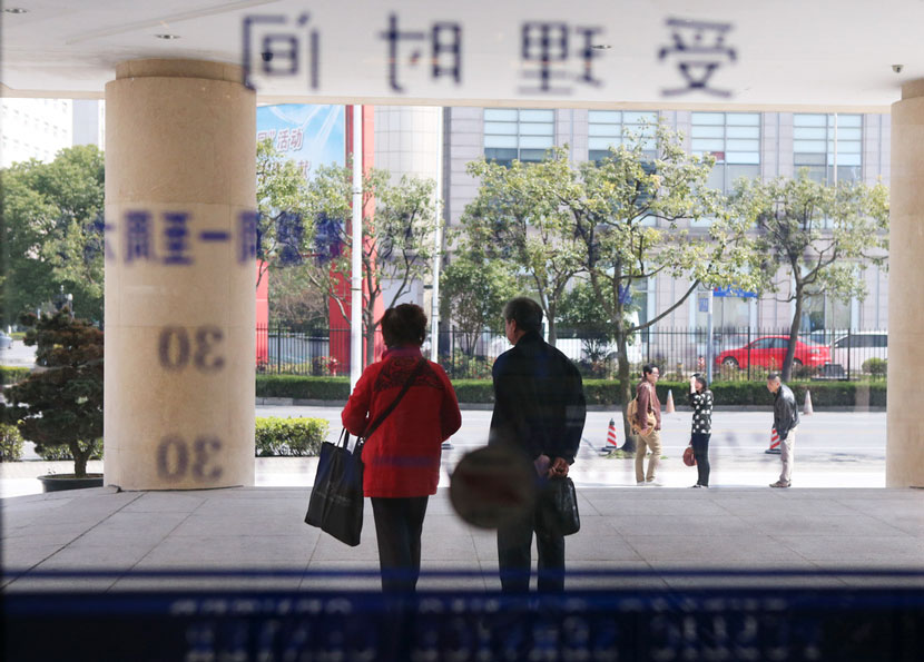 A couple walks out of the marriage registration office after finishing their divorce process in Shanghai, March 8, 2013. Zhang Xinyan for Sixth Tone