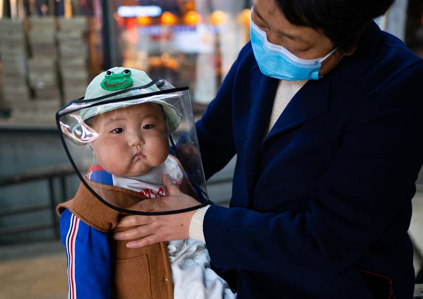 A woman adjusts a child's mask in Chongqing, April 2, 2020. Liu Song for Sixth Tone