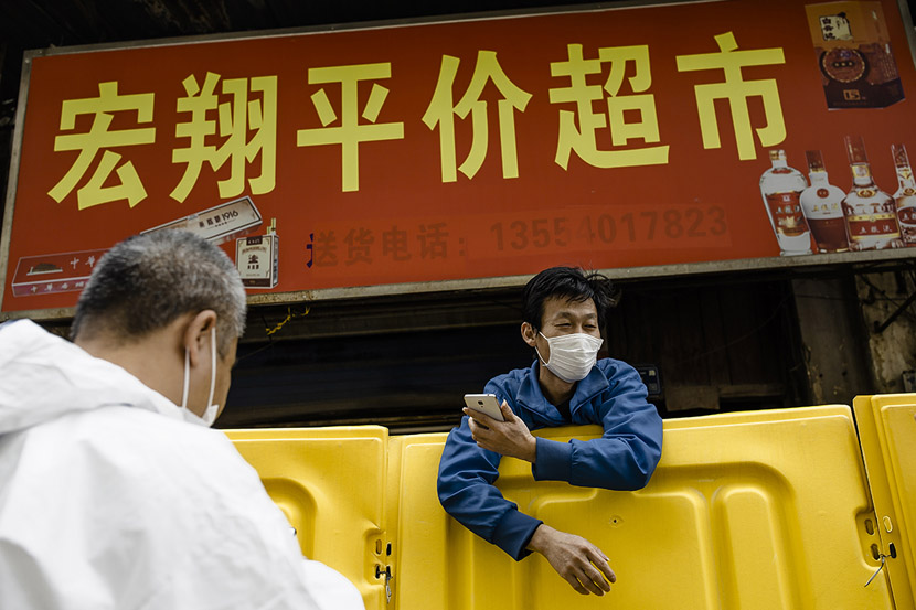 The owner of a grocery store leans over the yellow barrier in front of his shop to talk with a customer in Wuhan, Hubei province, March 22, 2020. Gerry Yin/Wild Photos