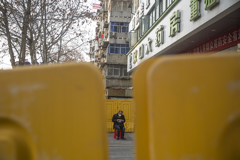 A senior waits outside a pharmacy in Wuhan, Hubei province, Feb. 23, 2020. Residents with special needs received gate passes that allowed them to go out and buy medicine at designated pharmacies. Gerry Yin/Wild Photos