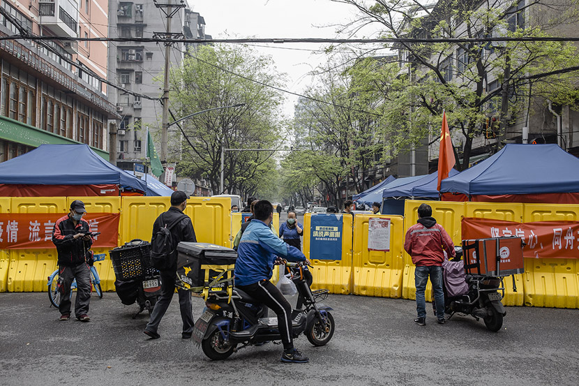 Delivery drivers wait for residents to pick up their orders outside a community in Wuhan, Hubei province, March 22, 2020. Drivers were not allowed to enter residential compounds during the lockdown. Gerry Yin/Wild Photos