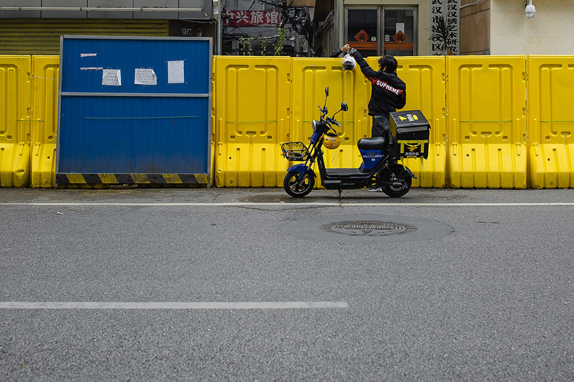 A delivery driver passes food over a barrier in Wuhan, Hubei province, March 22, 2020. Gerry Yin/Wild Photos