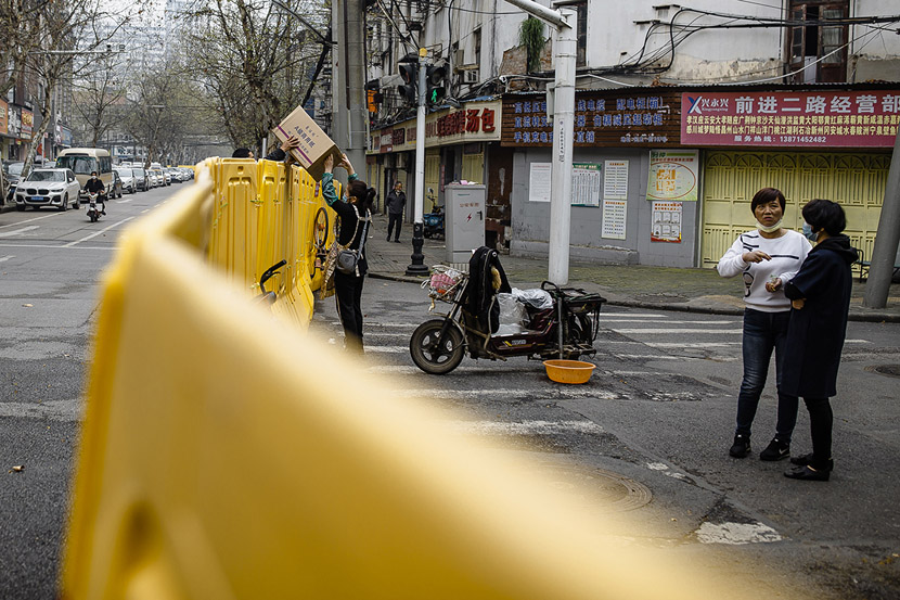 A delivery driver passes a package to a resident in Wuhan, Hubei province, March 22, 2020. Gerry Yin/Wild Photos