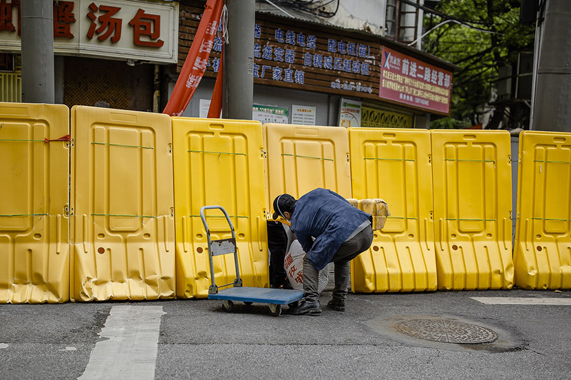 A man passes a heavy shipment through a hole in the wall's base in Wuhan, Hubei province, April 1, 2020. As time went on and the threat receded, residents began to find creative ways to break through their confinement. Gerry Yin/Wild Photos