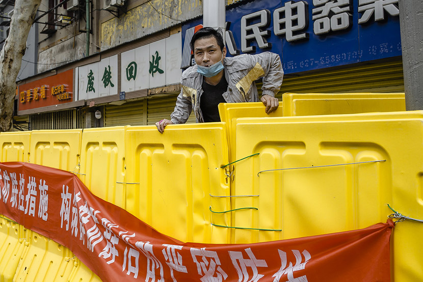 A resident vaults over a barrier to buy soy sauce in Wuhan, Hubei province, March 22, 2020. Gerry Yin/Wild Photos